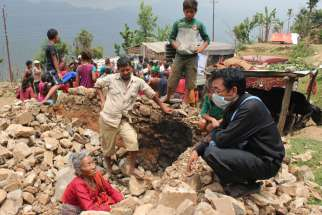 Father Ignatius Rai, vicar of Assumption Parish in Lalitpur, Nepal, chats May 9 with 85-year old Padam Kumari Magar, who had crawled out unscathed from the rubble of her stone home on Baretol Mountain after the April 25 earthquake.