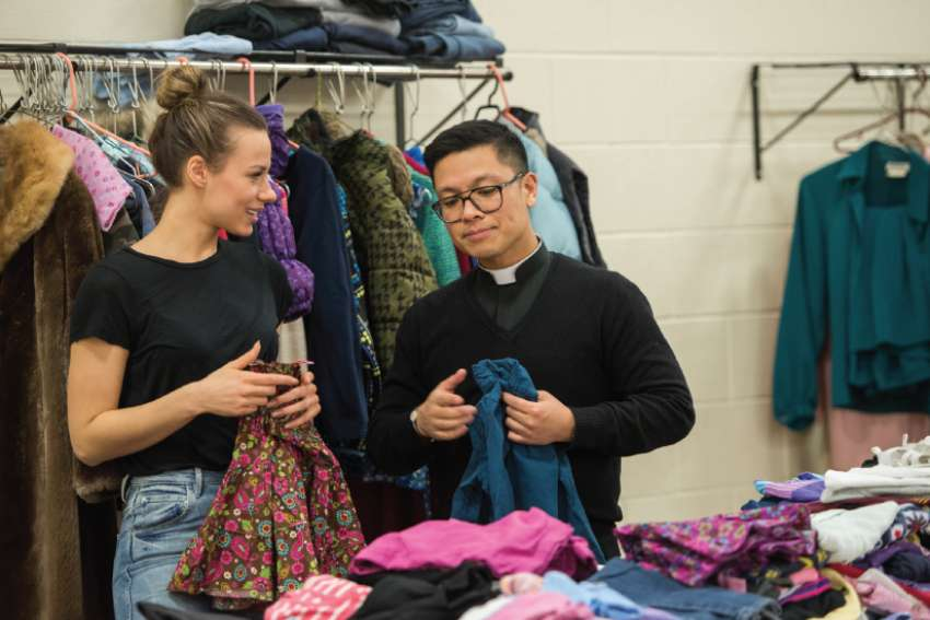 Benedicte LeMaître and Fr. Geoffrey Angeles sort through new clothes donated to St. Elizabeth's Closet at St. Mary's Cathedral.