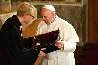 Pope Francis gives a gift to Rev. Jens-Martin Kruse during a visit to Christuskirche, a parish of the German Evangelical Lutheran Church, in Rome Nov. 15, 2015.