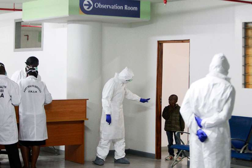 A Kenyan Port Health Services worker wearing full personal protective equipment commands a small boy, who is among nine Kenyans who were stranded in the Ebola-hit country Liberia, to return to an observation room for Ebola screening, as they arrive at Jomo Kenyatta International Airport Oct. 28 in Nairobi, Kenya.