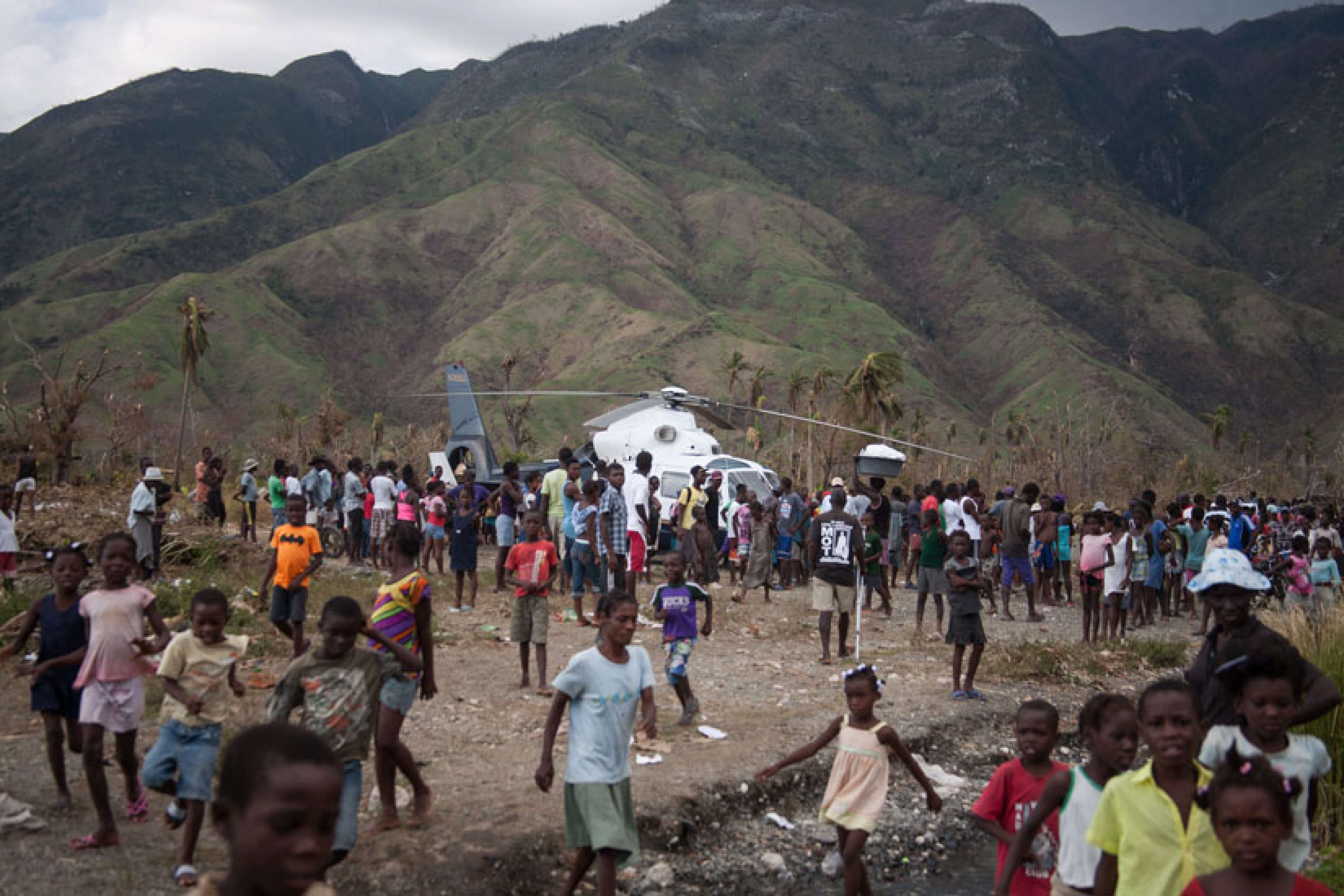 Victims of Hurricane Matthew walk towards an open area where an aid helicopter landed Oct. 10 in Tiborun, Haiti. As a sign of his closeness and concern, Pope Francis sent aid money to hurricane-stricken Haiti, to be distributed through the hardest-hit dioceses to assist flood victims.