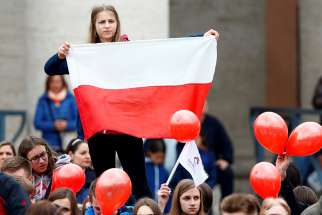 A girl holds a Polish flag as Pope Francis leads the Angelus March 19 in St. Peter's Square at the Vatican.