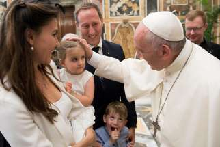 Pope Francis greets family members during an audience with participants in an international congress on protecting children in a digital world, at the Vatican Oct. 6.