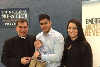 Father Frank Pavone, national director of Priests for Life, poses with Chris Caicedo, Andrea Minichini and their son, Gabriel Caicedo, following a news conference at the National Press Club in Washington Feb. 23 to call attention to a protocol to reverse RU-486 medical abortions.