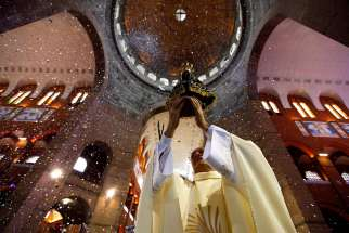 A priest holds an image of Our Lady of Aparecida during a Mass in Brazil's Basilica of the National Shrine of Our Lady of Aparecida Oct. 11, 2011. Pope Francis has declined Brazil president Michael Temer's invitation to visit for the 300th anniversary of the Marian apparition.