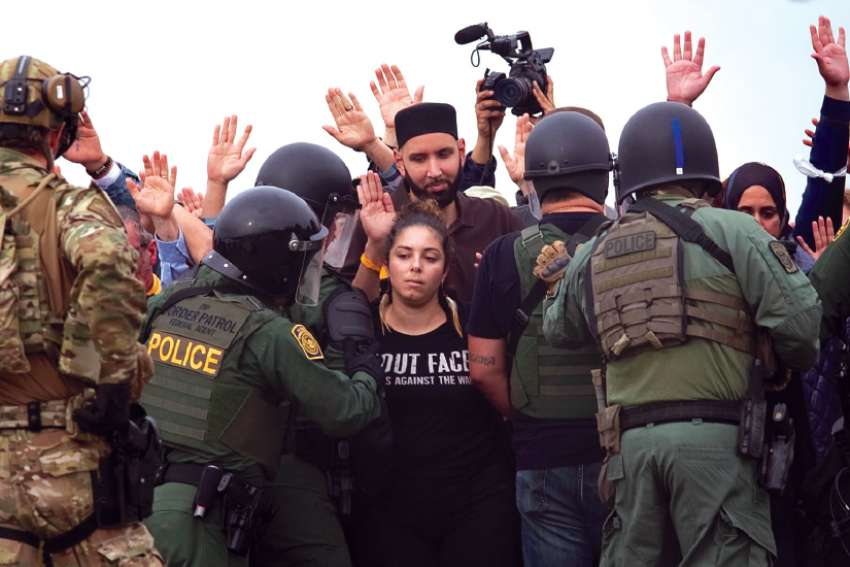 A woman prepares to be arrested by U.S. Border Patrol agents during a protest Dec. 10 at the U.S.-Mexico wall in San Diego in solidarity with the caravan of Central American migrants trying to reach the United States. The U.S. is one of the countries which didn't sight the UN migration compact.