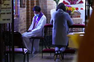 Father Jiha Lim listens to a penitent's confession March 7, 2021, at St. Aloysius Church in Great Neck, N.Y., during the COVID-19 pandemic. The Vatican says general absolution still is permissible where infections continue to rise.