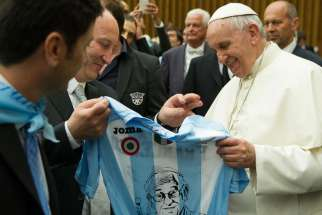 Pope Francis holds a jersey offered to him as a gift after leading a special audience for the Lazio sport association in Paul VI hall at the Vatican May 7.