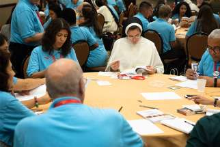 A woman religious is seen with delegates during a breakout session Sept. 21 at the Fifth National Encuentro in Grapevine, Texas.