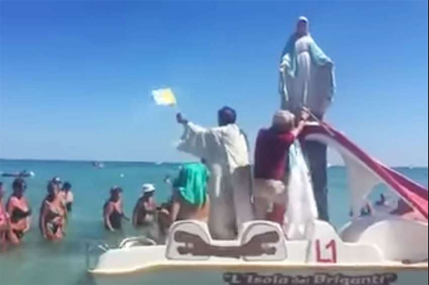Italian priest Father Mario Calogiuri came to beach of San Foca with a five-foot statue of the Virgin Mary on a paddle boat to bless the beachgoers.
