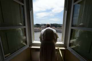 "Pope Francis looks out on an empty St. Peter's Square after leading the ""Regina Coeli"" prayer from his library in the Apostolic Palace at the Vatican May 10, 2020. The Sunday prayer took place without the physical presence of the faithful due to the coronavirus pandemic."