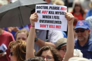 A woman holds a sign during a rally against physician-assisted suicide on Parliament Hill in Ottawa in this file photo.
