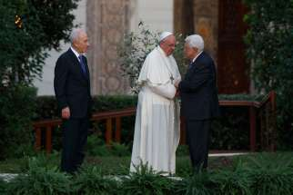Pope Francis greets Palestinian President Mahmoud Abbas as Israeli President Shimon Peres looks on during an invocation for peace in the Vatican Gardens June 8, 2014.