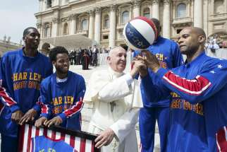 Pope Francis smiles as he plays with a basketball next to a members of the Harlem Globetrotters basketball team during his weekly audience in St. Peter's Square at the Vatican May 6.