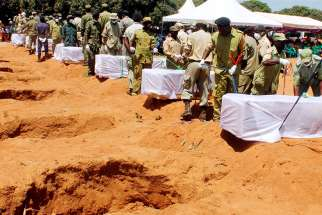 Tanzanian security agents in Ukara bury coffins Sept. 23 after a ferry overturned two days earlier in Lake Victoria.