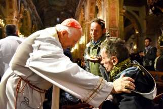Cardinal Ricardo Ezzati of Santiago greets homeless guests and invites them into the cathedral Aug. 19.