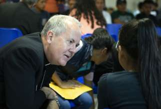 Bishop Joseph C. Bambera of Scranton, Pa., talks to an immigrant woman, recently released from U.S. custody, July 1, at a Catholic Charities-run respite centre in McAllen, Texas. A delegation of U.S. bishops has traveled to the Diocese of Brownsville, Texas, to learn more about the detention of Central American immigrants at the U.S.-Mexican border.