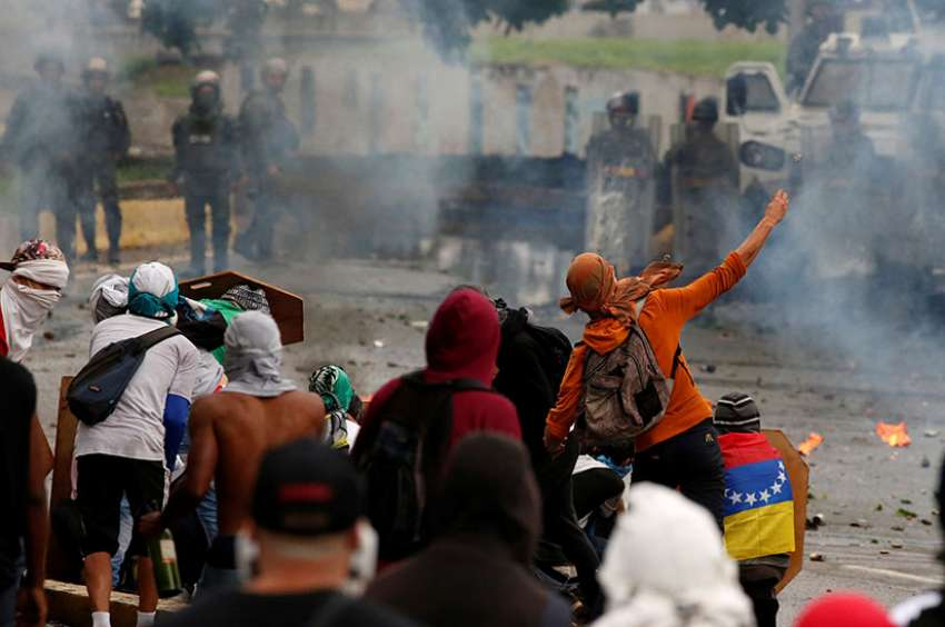 Demonstrators clash with riot security forces while rallying against Venezuela President Nicolas Maduro's government July 28 in Caracas.