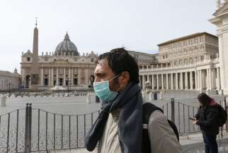 A man wearing a mask for protection from the coronavirus passes an empty St. Peter's Square at the Vatican March 10. The Vatican has closed St. Peter's Square and Basilica to tourists March 10 through April 3 in co-operation with Italian emergency procedures aimed at preventing the spread of the coronavirus.