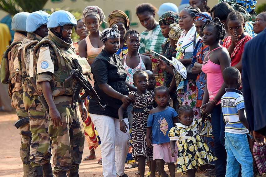 U.N. peacekeeping soldiers patrol alongside women and children in 2015 in Bangui, Central African Republic.