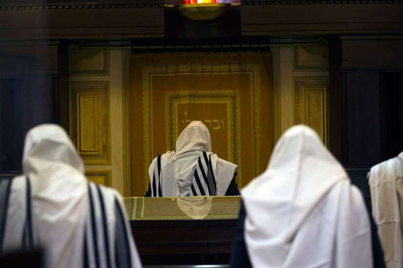 "Jewish worshippers covered in prayer shawls pray Nov. 19 at a synagogue in Jerusalem where two Palestinian militants killed four rabbis and a policeman. Pope Francis condemned the ""unacceptable episodes of violence"" in Jerusalem, episodes that ""do not sp are even places of worship."""