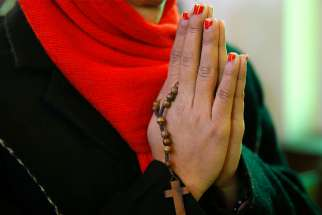 A woman prays at the Holy Family Church in Srinagar, India, Dec. 25, 2017.