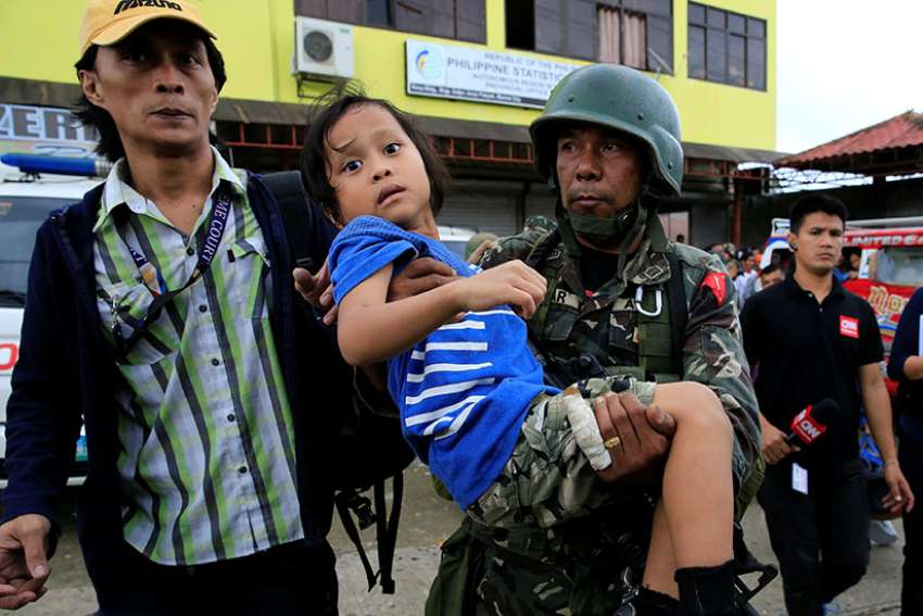 government soldier carries a girl who was rescued along with 20 other residents as government troops continued to fight Islamic militants May 31 in Marawi, Philippines.
