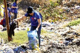 A volunteer picks up trash at Freedom Island, a marshland considered to be a sanctuary for birds, fish and mangroves in a coastal area of Las Pinas City, near Manila, Philippines. Few papal encyclicals have been as eagerly awaited as Pope Francis' upcoming statement on the environment.