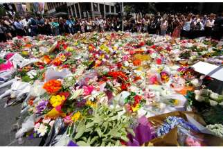 Members of the public look at thousands of floral tributes placed Dec. 16 near the Sydney cafewhere hostages were held for more than 16 hours. An Irish priest based in Sydney said he was amazed at how many people turned to prayer during the deadly siege.