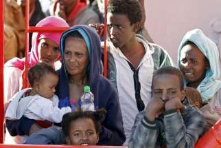 "Migrants wait to disembark from a tug boat in the Sicilian harbour of Pozzallo May 4. Pope Francis said that allowing migrants to die in boats is an ""attack on life,"" among others like abortion, euthanasia, war and terrorism."