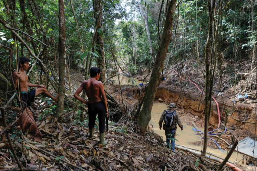 Yanomami Indians follow agents of Brazil's environmental agency during an operation against illegal gold mining on Indigenous land in the heart of the Amazon rainforest.
