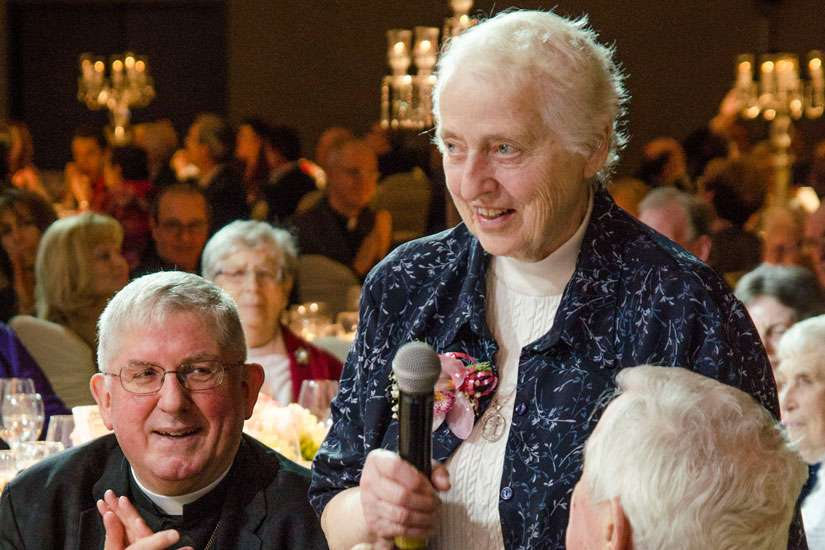 "Toronto Cardinal Thomas Collins watches as Sister Andrea Dumont accepts Catholic Missions' missionary award April 24 on behalf of all ""unsung heroes"" referring to all missionaries working in Canada."