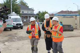 Bishop Vincent Nguyen (left), Imam Hamid Slimi and Rabbi Baruch Frydman- Kohl are dressed for action on the Habitat for Humanity site.