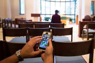 This photo illustration shows someone using a cellphone inside a Catholic chapel in Washington Oct. 27.