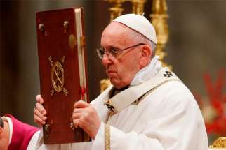 Pope Francis raises the Book of the Gospels as he celebrates Christmas Eve Mass in St. Peter's Basilica at the Vatican Dec. 24.