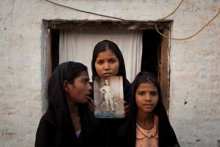 The daughters of Asia Bibi pose in 2010 with an image of their mother while standing outside their residence in Sheikhupura, Pakistan.