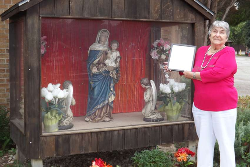 Jennie McRae poses at Sts. Martha and Mary Parish in Mississauga with the letter she received from Cardinal Thomas Collins after completing her decade-long trek around the vast territory of the archdiocese to visit all its churches.