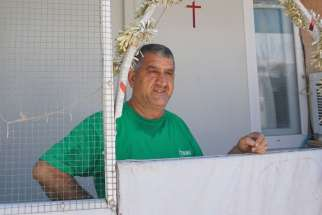 An Iraqi Christian spruces up his shelter July 24 with a cross and other Christian symbols at the the Ashti camp for internally displaced Iraqis in Ainkawa. Some 7,000 Christians, mainly Catholics, were forced to escape the Islamic State assault on Mosul and their surrounding villages two years ago and fled to Ainkawa, a Christian enclave of the Kurdish capital, Irbil.