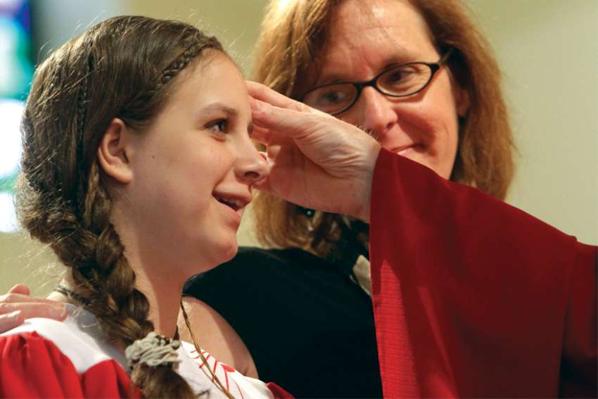 A young girl is anointed during Confirmation while her sponsor looks on.