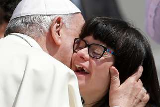 Pope Francis embraces a woman as he meets the disabled during his general audience in St. Peter's Square at the Vatican June 13.