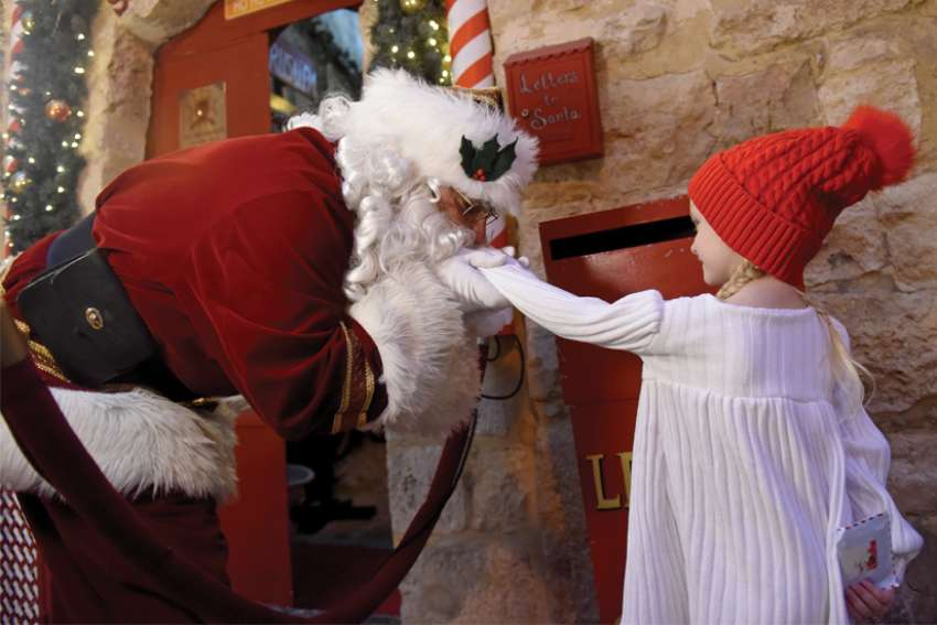 Palestinian Catholic Issa Kassissieh, known as Jerusalem Santa, wearing a protective mask, kisses the hand of four-year-old Mia Tusko at the entrance to Santa's House Dec. 7. The house was created out of his family's 700-year-old home in the Old City of Jerusalem.