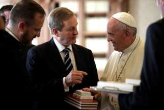 Pope Francis exchanges gifts with Irish Prime Minister Enda Kenny during a private audience at the Vatican Nov. 28.