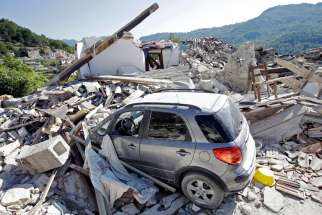 A car covered by debris is seen near a collapsed house in Pescara del Tronto, Italy, Aug. 26. Pope Francis announces his intention to visit towns struck by an Aug. 24 earthquake, which left hundreds dead.