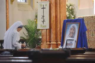 A member of the Missionaries of Charity honors the four sisters who were murdered in Yemen March 4 during a memorial Mass in New York City April 1.