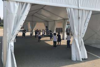 Father Serra School students take part in gym class under a tent in the school yard.