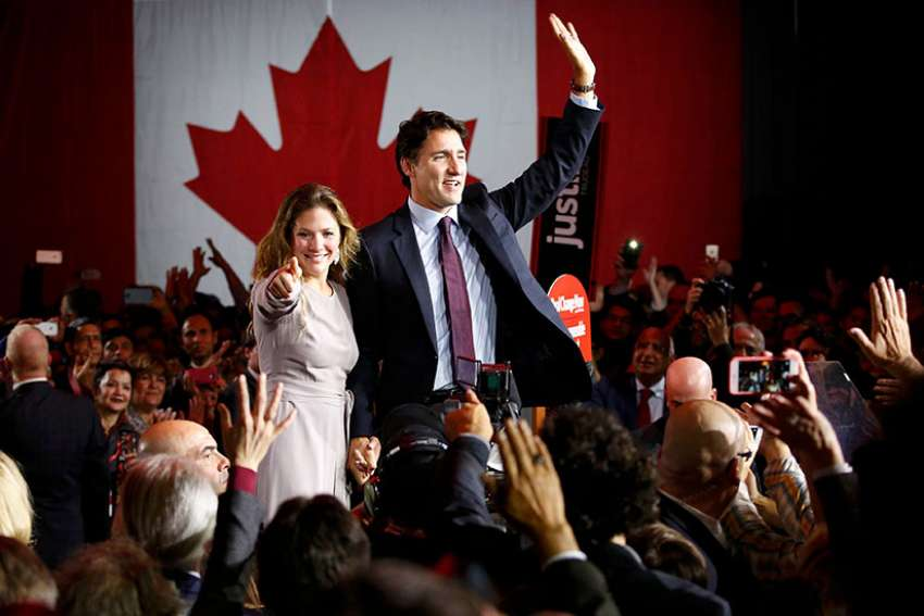 Liberal Party leader winner Justin Trudeau and his wife Sophie Gregoire wave during victory speech in Montreal, Oct. 19, 2015.