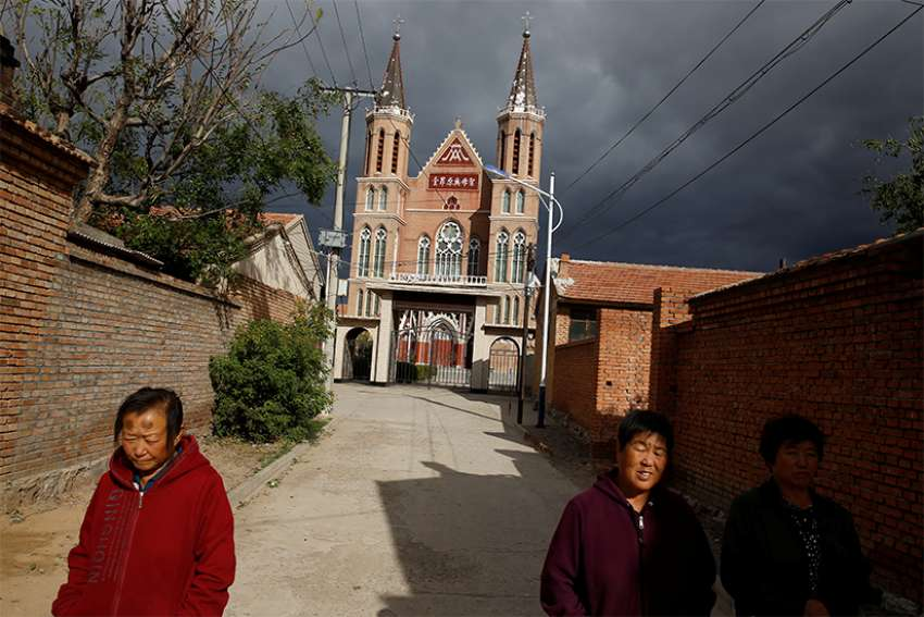 Villagers walk near a Catholic church in the village of Huangtugang, Hebei province, China, Sept. 30, 2018. In a new book, the Vatican secretary of state, Cardinal Pietro Parolin, writes that the Vatican's recent agreement with the Chinese government was motivated by a desire to spread the Gospel and assure freedom of the church.
