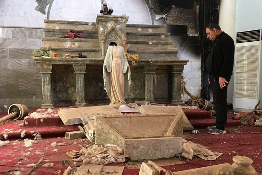 A Catholic church destroyed by Islamic State militants in Karamdes, Iraq, is examined by a priest following the predominantly Christian town's 2016 liberation.