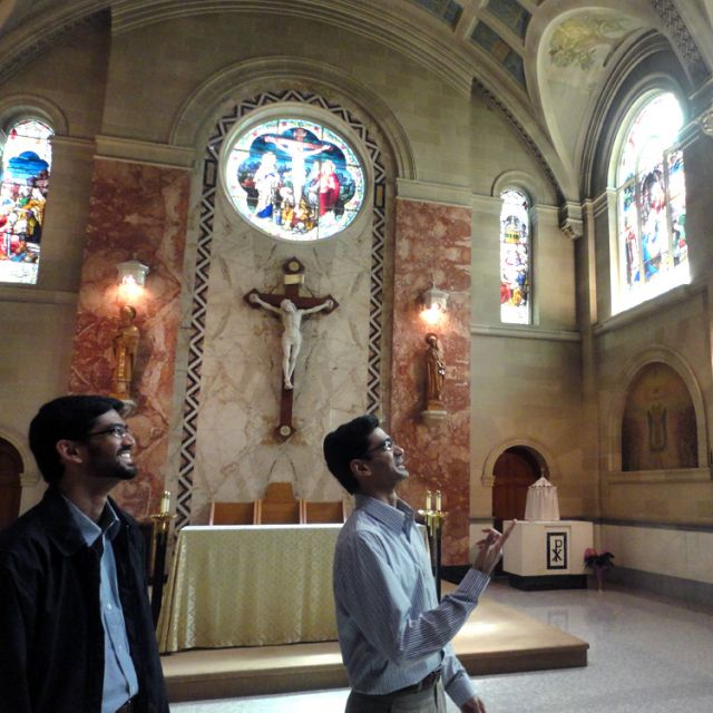 Ryan Alemao, a first-year seminarian at St. Augustine's Seminary, describes the designs of stained glass windows in the chapel as fellow first-year seminarian, his younger brother Favin, looks on.