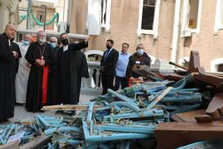 Cardinal Pietro Parolin, Vatican secretary of state, with red sash, views the damage at Sacred Heart School near Beirut's port area Sept. 4, 2020, one month after the city suffered double blasts.